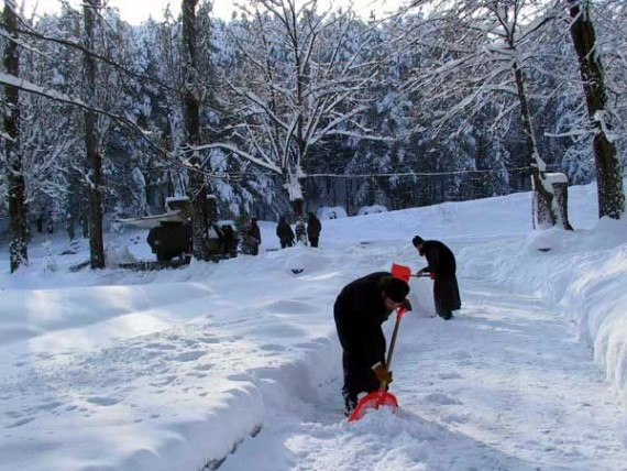 Cleaning snow - Italian guards in the background, Visoki Decani Monastery monks, Serbia