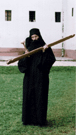 Knocking with a hammer on a wooden semantron - a traditional Orthodox device for announcing the time of prayer, Visoki Decani Monaster